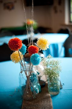 I love these pom poms as table centerpieces (actualy this whole table display is perfect)! Even those blue table cloths. Each table will have its own color scheme based on different Wes Anderson movies .