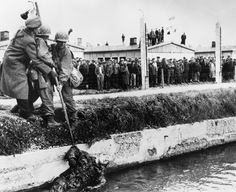 """""""When American troops liberated prisoners in the Dachau concentration camp, Germany, in 1945, many German SS guards were killed by the prisoners who then threw their bodies into the moat surrounding the camp."""" (AP)"""