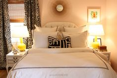 Gorgeous bedroom with ivory button tufted headboard against pale pink walls.