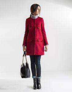 Abrigo corto rojo de mujer, cuello redondo, cierre frontal con broches ocultos, dos tapetas decorativas en parte alta y dos bolsillos tapeta laterales en parte baja.