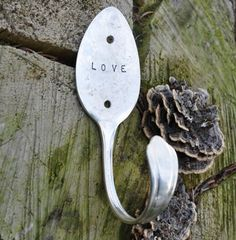 silver plated table spoon bent and stamped into a coat hook.