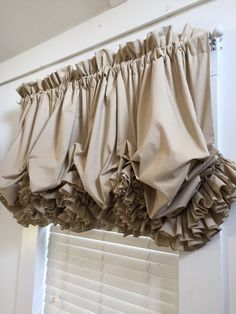 Fully lined, double ruffled balloon curtain made of of Roc-Lon Tea Dyed Light Muslin. Tea dyed muslin is a khaki color. It is a stationary balloon curtain and does not raise up and down but I can make it any length you want. This one is 27 inches from the rod down to the end of the ruffle. It is 90 inches wide before gathering on the rod and will fit any standard sized window up to 45 inches wide or a bit wider. Email with questions. Thanks for visiting