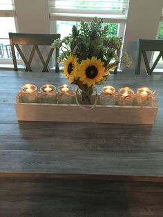 Farm table centerpiece. Took a custom made planter box and 7 large mason jars. Tied a rope like ribbon around the outer 6 and covered bottom with assorted green gem stones. Filled with water and added floating candles. Created a sunflower arrangement at Michaels for center jar.