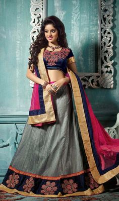 Ash gray net lehenga with contrast choli and dupatta is perfect combo for festive season party. Lehenga is embellished with woven lace, silk thread embroidered motifs on blue patch in the hem and scattered crystal stones which gives you an elegant look. Contrast pink net dupatta is embellished with golden woven lace and scattered crystal stones.  Lehenga is coming with contrast navy blue velvet stitched choli as shown in the picture. #IndianLehengaCholi