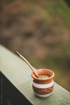 A cup of yerba mate tea in gourd and bombilla on a wooden balcony overlooking the woods