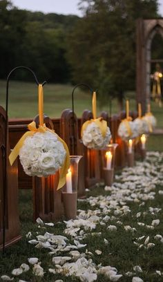 A wedding aisle decorated with candles, petals and white rose pomanders with yellow ribbon. #wedding #aisle