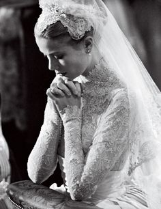 Grace Kelly, in a gown by MGM costume designer Helen Rose, kneeling at the altar during her wedding at Saint Nicholas Cathedral to Prince Rainier III of Monaco in April 1956.    Photo: Bettmann/Corbis