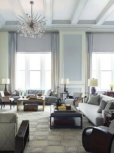 Living room by Steven Gambrel with high coffered ceilings, a modern spikey chandelier, grey-lavender painted walls to created a panel effect, floor length curtains, grey sofas and matching armchairs, a leather ottoman has been turned into a coffee table and a greyish lavender area rug covered in squares.