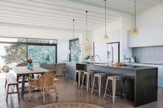 contrasting island from white cabinetry and soft grey tiles. Pendant lights over island.