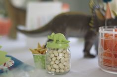 Baby food jar + small plastic dino + spray paint + candy (dino eggs) = adorable party favor
