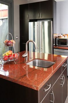 A square center island with an undermount sink and red dragon granite counters.