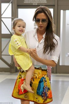 Victoria showed off her toned legs in a skirt with a white blouse as she carried her adorable daughter through the airport