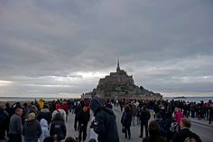 People gather on the walkway leading to Mont-Saint-Michel on March 21, 2015 in France