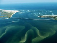 Cape Hatteras National Seashore  Photograph by David Alan Harvey    Swirling sandbars wend their way across Oregon Inlet, part of Cape Hatteras National Seashore in North Carolina's Outer Banks. The Outer Banks—a 200-mile-long (322-kilometer-long) chain of low, slim barrier islands—arc out from the mainland, protecting the coast and shallow sounds from the battering Atlantic.