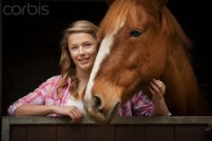 Teenage girl with horse in stables