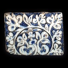 Egypt or Syria.  A stone paste tile, the interesting design, painted in underglaze black and cobalt-blue on a white ground, is vigorously and freely drawn. The branch with its attendant leaves wrap around a central design depicting abstract plants. In between the foliage, are small precise fish-scale motifs in cobalt-blue.  First half of the 15th century