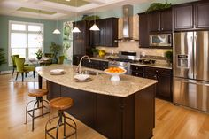 kitchen/dining room open layout design with dark cabinets, light colored granite and stainless steel appliances