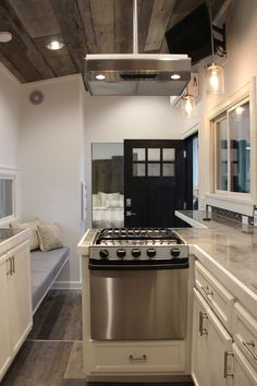The L-shaped kitchen features upper and lower cabinets, a full size refrigerator with bottom freezer, and a propane oven with a three-burner stove.