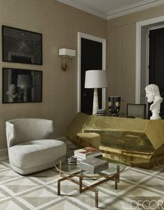 A lamp by Arteriors tops a brass desk by Bardeaux Meuble in the study; the armchair is by Baxter, the photo graphs are by Dune Varela, the walls are upholstered in a Donghia fabric, and the rug and cocktail table are custom made.