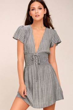 There are nothing but good times ahead in the Ahoy Grey Striped Lace-Up Dress! Lightweight woven rayon, in a grey and white striped pattern, creates a plunging V-neck and back (with back button closure), and ruffled short sleeves. Smocked, lace-up waist tops a flirty mini skirt. #NothingButDresses