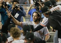 San Francisco Giants starting pitcher Madison Bumgarner, center, is congratulated by teammates after hitting a two-run home run during the third inning of a baseball game against the Los Angeles Dodgers Tuesday, Sept. 23, 2014, in Los Angeles. (AP Photo/Jae C. Hong)