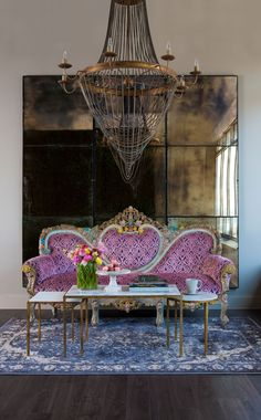 foxed mirrors, recovered settee, nesting coffee tables in two shapes & an edgy chandelier make a striking seating area