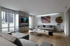 suggestion très moderne et design, amenagement salon en gris et blanc, peinture murale blanche, canapé et meuble tv gris, jolies tables à café blanches