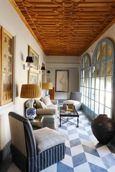 Wood ceiling detail, arched windows, lamps, sconces with black shades, slipper chairs -Lorenzo Castillo