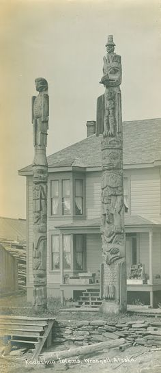 """a view of Kadashan house and totem poles at the village Kaachxan.áak'w (translated as Little Lake Accessible to the People), labeled """"Kadeshan Totems, Wrangell, Alaska,"""" photo by Worden, circa 1900."""
