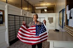 Arcola, Mississippi, Postmaster folding the flag at the end of the day. - The Deep South, As Seen Through the Eyes of Renowned Photographer Steve McCurry | Arts & Culture | Smithsonian