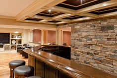 Breathtaking recessed panel ceiling with halogen lighting over wet bar complimented by cultured stone wall and solid oak bar rail.