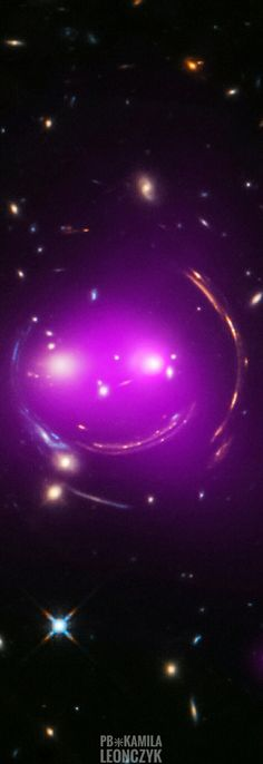 """Smile Please - Gravity's Grin Nicknamed the Cheshire Cat galaxy group, the group's two large elliptical galaxies are suggestively framed by arcs. The arcs are optical images of distant background galaxies lensed by the foreground group's total distribution of gravitational mass. Of course, that gravitational mass is dominated by dark matter. The two large elliptical """"eye"""" galaxies represent the brightest members of their own galaxy groups which are merging."""