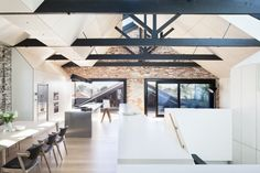 Gorgeous, exposed wood beams. Bright natural lights from well-placed skylights. White and grey color scheme. All make this warehouse conversion inspiring.