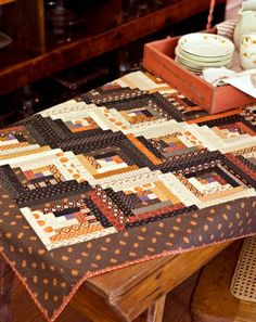 Using an abundance of prints in fall hues, whip up a Log Cabin table topper that has a Straight Furrows setting. - still want to do a log cabin quilt. Love the brown/orange combination. Log Cabin Quilt Pattern, Log Cabin Quilts, Log Cabins, Table Topper Patterns, Table Toppers, American Patchwork And Quilting, Halloween Quilts, Fall Quilts, Miniature Quilts