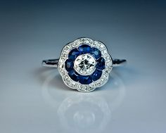 Antique Sapphire and Diamond Platinum Engagement Ring, circa 1910. The ring is centered with an old European cut diamond surrounded by a row of tapered calibre cut natural sapphires and further set with a border of old cushion cut diamonds.