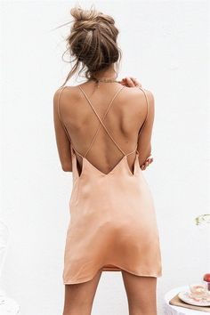 The easy-to-wear Nia Slip Dress is made from a matte silky fabric in a peach hue. It is a slip style and features a V neckline and low back with strappy detailing. Complete the look with tan mules and gold accessories! By Sabo Skirt.