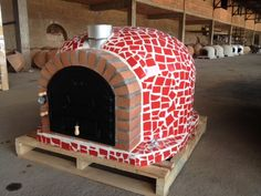 wood fired oven with cast iron door and tile mosaic