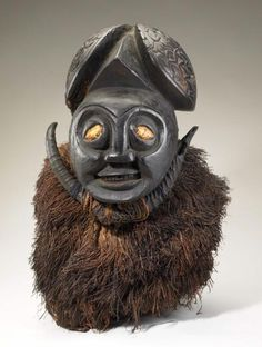 Africa | Crest/Skull Mask.  Bamum peoples.  Cameroon | Wood, horn, plant fiber, spider silk | This crest mask is power personified. Ground spiders are used in divination practices in the Cameroon Grassfields region as a way of gaining access to divine knowledge. The eyes of this mask are covered with silk taken from spider egg sacs or the lining of the nest of the ground-dwelling tarantula.