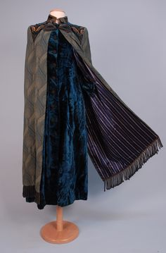 298   LADY'S EMBROIDERED VELVET AND WOOL COAT/CAPE, c. 1900. Aquamarine velvet, the back, stand-up collar, shoulder and back hem lavishly decorated with couched embroidery, two hook & eye neck closures over nine crochet buttons (one missing), blue & gold brocade cape attached at shoulders and alongprincess seams at back, braided cord over hook & eye, heavy braid fringe, striped quilted silk lining, Ehrich Bros label. Shoulder 16, waist 30, length 53. Shoulder seam open, tiny hole, excellent…