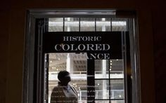 """A woman stands in the doorway of then new Historic Colored Entrance at the Lyric Theatre. Preservationists had to decide whether to keep reminders of The Lyric's discarded color line before they unveiled an $11 million restoration of the 102-year-old theater, which had been closed for decades. In this case, they chose to highlight the history, installing a glass door with the etched words """"Historic Colored Entrance"""" in the lobby wall so patrons can peer into the past. (AP Photo/Brynn…"""