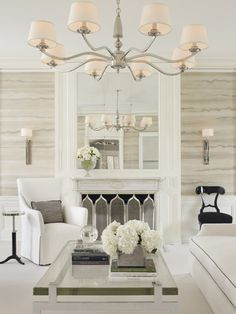 Love the walls source: Lichten Craig Architects Elegant living room with faux bois wallpaper, fireplace, polished nickel chandelier with linen drum shades, white slipcover chair, glass-top cocktail table and white sofa with black piping.