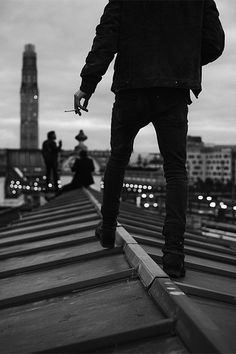black and white photo. Male model on a rooftop. all black look