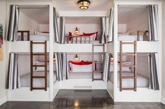 These white U-shaped bunk beds in a cottage are a custom built in creation featuring gray and white striped bedding with red accent pillows.