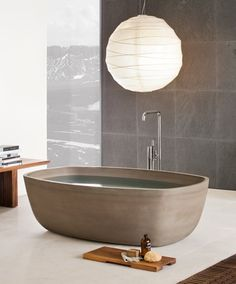 The bath tub in this image will provide a asian design in the bathroom. The curved shape in this bath captures the earthy/ neutral texture and colour,which is what asian design is all about. Having the bath placed on  the floor without the legs allows a natural feel.