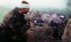"""May 1995 Photograph: Eric Bouvet  - """"I was with a Russian special commando. They were torturing, killing and raping. I saw them do it, and I couldn't stop them. This is the morning after a night that left four men dead and 10 wounded. I discovered a dead Chechen four metres from me when I got up in the night. We started out as 60 and came back 30 – one in two people injured or killed.The guy with the bandage on his head has lost his friends."""""""