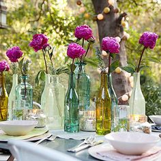 I love the subtle variations of the glass colors in this simple place setting of gorgeous Fuchsia Peonies in wine bottles!