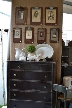 unique way to display old photos; use clipboards-  Note from Carolyn: great in casual lifestyle rooms, the effect requires multiple clipboards in lieu of frames good idea for displaying kids artwork often.