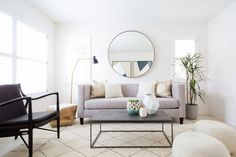 Serene living room with a large round mirror, a large Morrocean area rug, and a gray sofa