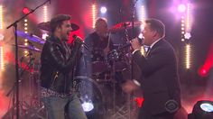 James Corden and Adam Lambert got into a good old fashioned staged singing competition on The Late Late Show Thursday night to find out who would be a better frontman for legendary rock band, Queen. They were even joined by two original members of the band: guitarist Brian May and drummer Roger Taylor. Lambert has been performing with Queen off and on since 2011, but Corden did his best to prove that he would be the better frontman.