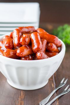 A white bowl of barbecue little smokies against a dark wood background. There are jsix square plates out of focus in the background and a green plant.